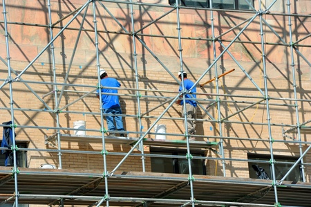 Two men stand on scaffolding and work on exterior repairs on the City Building in downtown, Asheville, North Carolina. Zdjęcie Seryjne