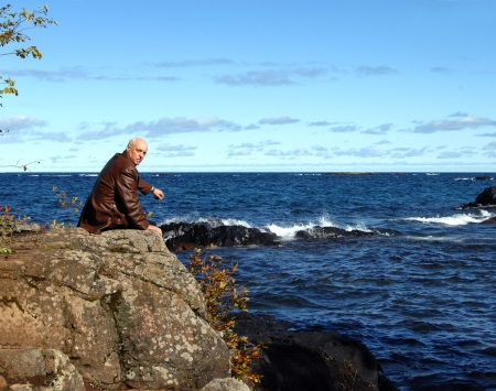 Retired man sits on Lake Superiors rocky shoreline in Upper Peninsula, Michigan.  He is sitting on a rocky cliff overlooking the deep blue water.  Cold Fall weather makes his coat a necessity. photo