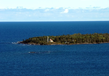 Copper Harbor Lighthouse sits on tip of the Keweenaw Peninsula. It is surrounded by the blue water of Lake Superior. photo