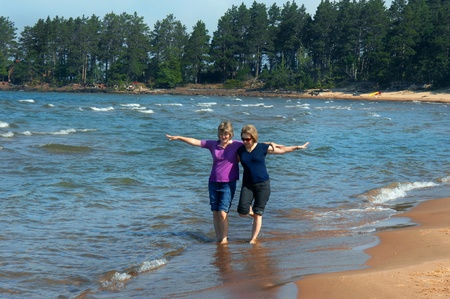 Two women revisit childhood and games while playing in the waves on the shores of Lake Superior in Upper Peninsula, Michigan.  They are barefoot with jeans rolled up kicking the waves. photo