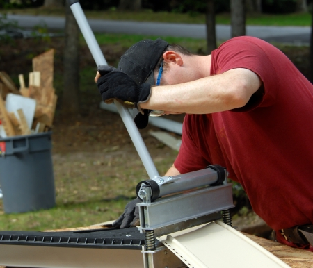 Young construction worker uses equipment to cut pieces of siding for home improvement project.  He is wearing a red T-shirt and wearing a tool belt, hat and safety glasses.