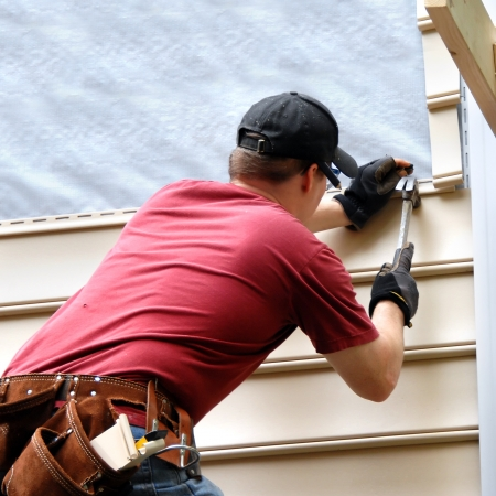 cladding: First time home buyer works to install siding on his new home.  He is hammering into place a sheet of siding.  He has on a red shirt and is holding hammer and nail.