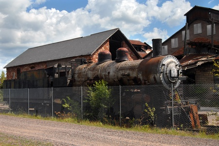 abandoned warehouse: Historic locomotive sits inside fence at the Quincy Copper Smelter in Hancock, Michigan.   Stock Photo
