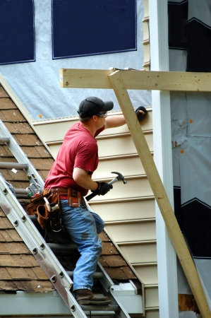 Young carpenter installs new sideing on a two story home.  He is holding a hammer and nail. Standard-Bild