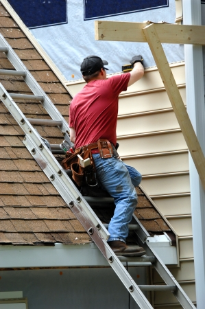 cladding: Young carpenter remodels aging home.  He is installing siding and is using a level to be sure installation is precise.  He is standing on a ladder on rooftop. Stock Photo