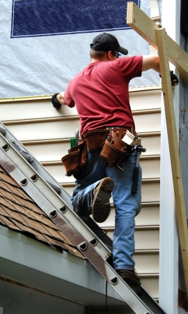 Jonge huiseigenaar renovaties zijn ouder huis door het installeren van gevelbekleding. Deze doe-het-zelver is meet voor het volgende vel te installeren.