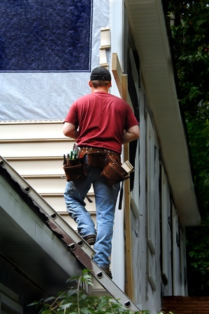 Homeowner does a self installment job on his home siding.  He is standing on a ladder attached to the roof of his home.