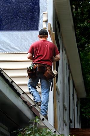 Huiseigenaar doet een zelf afbetaling baan op zijn huis opruimen. Hij staat op een ladder bevestigd aan het dak van zijn huis. Stockfoto