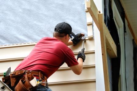 Jonge huiseigenaar installeert gevelbeplating naar zijn huis. Hij houdt een hamer en het dragen van een hulpmiddel riem.