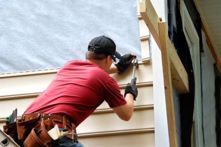 cladding: Young homeowner installs siding to his home.  He is holding a hammer and wearing a tool belt.