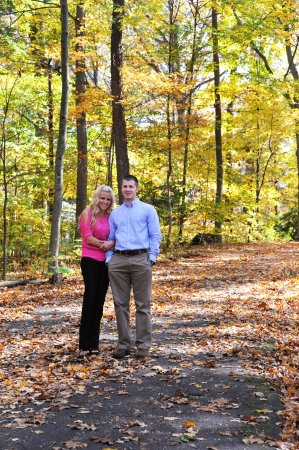 khakis: Couple stroll down path littered with fallen leaves.  Overhead a tunnel of yellow glows in the sunlight.  Both are dressed neatly and both are smiling happily.