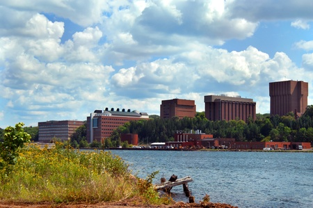 Buildings on the campus of Michigan Tech overlook Portage Lake in Houghton, Michigan.  Flowers bloom along shoreline. photo