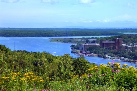 upper peninsula: View of Michigan Technological College located in Houghton, Michigan.  Wildflowers bloom in foreground and Portage Lake surrounds picturesque campus. Stock Photo