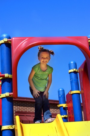 Little girl enjoys recess time on the playground equipment. She is standing inside a large, blue metal loop attached to a bright yellow slide. Banco de Imagens