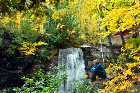 Adult female rests in front of Hungarian Falls on the Keweenaw Peninsula of Michigan.  Autumn yellow surrounds hiker with her thoughts and the splashing waterfall. photo