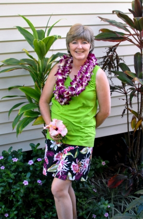 leis: Tourist smilingly displays her flower leis and tropical print skirt  Stock Photo