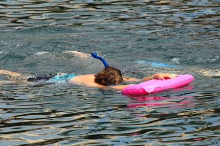 snorkle: Beginning snorkler clutches a bright pink float as she snorkles face down at a resort on the Big Island of Hawaii  Stock Photo