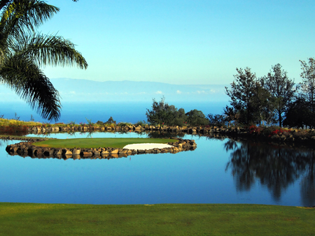 Golfing in paradise includes Kohala Mountain backdrop, tranquil water reflecting blue sky and lush green grass   Throw in tropical trade winds of the Big Island of Hawaii and it is truly paradise  photo