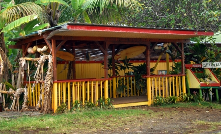 surf shop: Gaudy roadside fruit stand catches the eye of vacationers looking for refreshment on the Big Island of Hawaii   Surf boards and floats hang from the rafters  Stock Photo