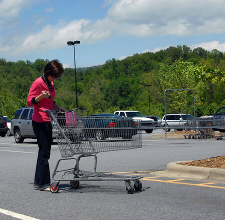 Mature and attractive woman checks her purse and keys as she pushes a shopping cart across parking lot   She is checking her  to do  list before entering store