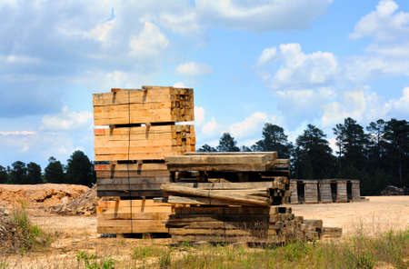 Stack of newly cut lumber sits in stacked pallets ready for distribution   Stack sits on open yard at sawmill