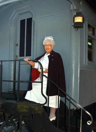 Retired nurse models her old school uniform and cape.  She is standing on the steps of a caboose.                               photo