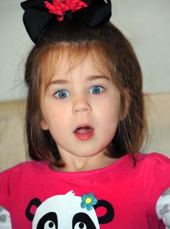 bow hair: La ni�a muestra su asombro con los ojos muy abiertos y la boca abierta Ella est� usando una camisa de color rosa y el pelo negro arco adornado con cinta rizada de color rosa