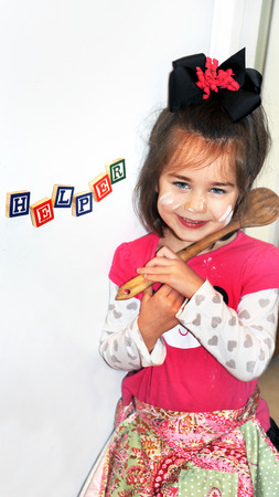 Little girl poses in front of refrigerator in her home   Magnetic blocks spell  Helper   A big smile lights her face complete with a sprinkle of flour on face and shirt   She is holding a wooden spoon    Stock Photo - 25707082