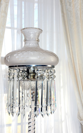 Elegant vintage light sits in front of a curtained window.  Globe is white with etchings and crystals are clear and dangle from edge of globe.