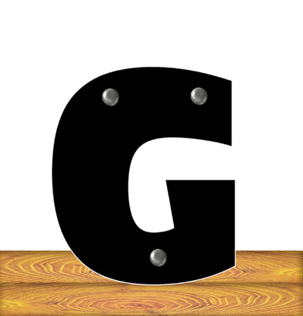 The letter G, in the alphabet set Construction, is black with silver nails embedded in letter.  Letter sits on wooden planks.