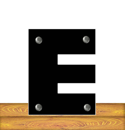 The letter E, in the alphabet set Construction, is black with silver nails embedded in letter.  Letter sits on wooden planks. photo