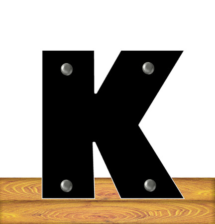 embedded: The letter K, in the alphabet set Construction, is black with silver nails embedded in letter.  Letter sits on wooden planks.