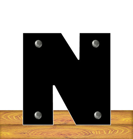 embedded: The letter N, in the alphabet set Construction, is black with silver nails embedded in letter.  Letter sits on wooden planks. Stock Photo