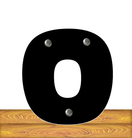 embedded: The letter O, in the alphabet set Construction, is black with silver nails embedded in letter.  Letter sits on wooden planks.