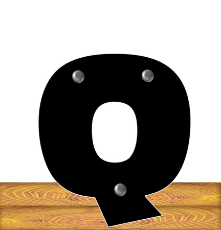 The letter Q, in the alphabet set Construction, is black with silver nails embedded in letter.  Letter sits on wooden planks. Stock fotó