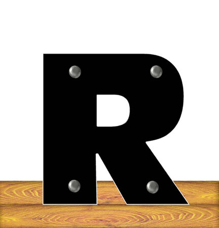 The letter R, in the alphabet set Construction, is black with silver nails embedded in letter.  Letter sits on wooden planks.