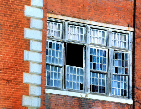 health facility: Broken windows look into the Old South Carolina State Hospital in Columbia, South Carolina.  Brick and stone frame windows of historic mental health facility. Stock Photo