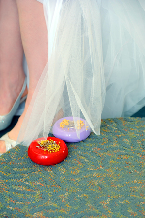 hem: Bride holds her wedding dress up to be pinned and hemmed.  Stick pin caddies sit on bridal podium.  Pins have yellow tops.