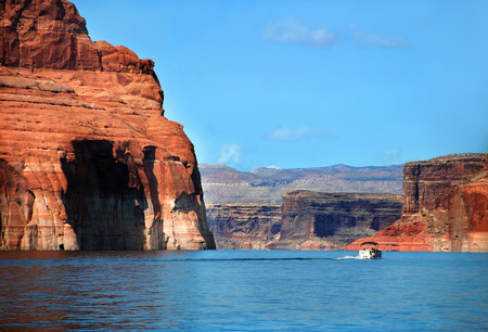 disappears: Boat speeds past beautiful scenery as sandstone cliffs rise from the waters of Lake Powell.  Waterway disappears into the distance.