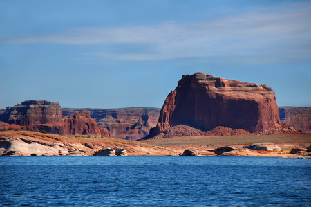 rugged: Red Sandstone cliffs surrounding Lake Powell add color to the Utah scenery.  Rugged cliffs tower over the shoreline.