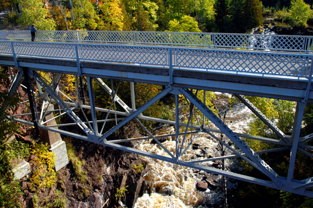 eagle falls: Eagle River Falls is observed by a woman standing on the Eagle River Bridge in Upper Peninsula, Michigan.  Autumn colors hillside and gorge.