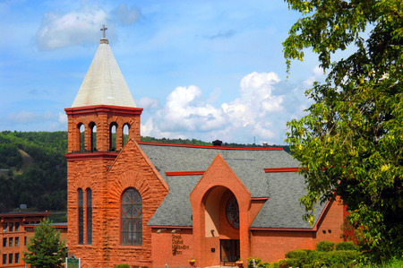 methodist: Quincy Hill serves as background for Grace United Methodist Church in Houghton, Michigan.  The Methodist church is composed of Jacobsville sandstone and built along the Richardsonian Romanesque style. Stock Photo