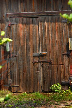 barn doors: Closed barn doors have metal hooks and hinges.  Weathered boards are dented and aged. Stock Photo