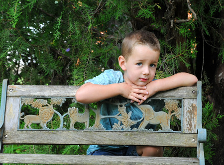 somber: No one knows a childs thoughts behind his eyes.  This young boy leans against a wooden park bench and considers the problems of his young world.