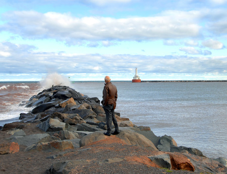 breakwater: Man stands braving wind and rough water to watch waves at the breakwater of the Portage Canal on Lake Michigan.  Light in background is the North Entry Light into the canal.