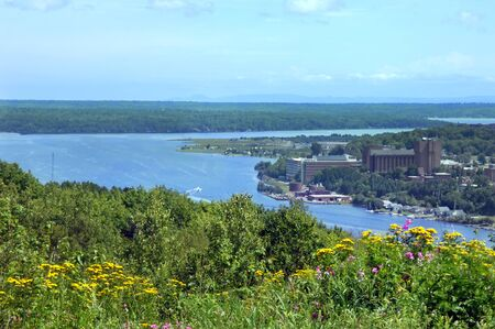 portage: View of Michigan Technological College located in Houghton, Michigan.  Wildflowers bloom in foreground and Portage Lake surrounds picturesque campus. Stock Photo