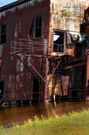 suction: Abandoned copper suction dredge lays in the waters of Torch Lake near Mason, Michigan in the Upper Penninsula.  Graffiti defaces the tin exterior and rust takes its tole. Stock Photo