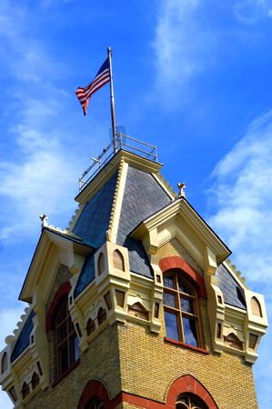 mansard: 120 year old, Victorian era county courthouse in Houghton, Michigan is designed with local red sandstone and Lake Superior copper for the roof. Flag flies on mansard roof.