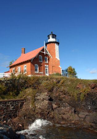 lake dwelling: Eagle Harbor Lighthouse sits proudly on a cliff overlooking Lake Superior on the Keweenaw Peninsula, Michigan.  A brick structure with lighthouse keeper dwelling attached.