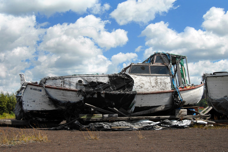 upper peninsula: Lake Superior fishing boat sits retired from service near Ripley, Michigan, in the Upper Peninsula.  The boat has cracked and peeling paint, broken window andhas rotting tarps covering it. Editorial